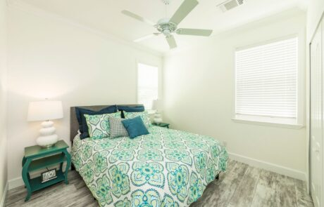 Queen bed with nightstand. Brightly lit and ceiling fan. Opens larger image in a gallery.